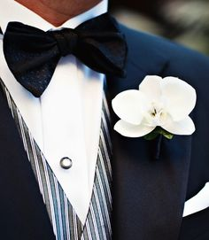 A black bow tie and white orchid boutonniere are an ever-elegant choice for a groom.
