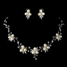 "This beautiful floral design necklace and earring set are arranged with freshwater pearls set in floral design and adorned with clear rhinestones. Accompany with matching french clip (not clip-on) pierced earrings for dashing brides, this lovely and charming necklace and earring set will complement any wedding grown and wedding inspired look.  Size: Necklace - 16"" (Length)  Earrings - 1"""