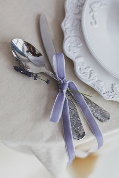 Silverware set up with white plates.