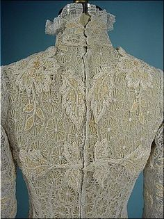 c. 1908 All Lace Princess Trained Gown with Wool Inserts. Princess shape, all spider lace gown with high frilly lace neck and train. The inserts are a woven ecru wool. Detail