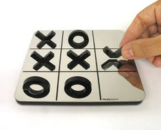 "Designed by Shahar Peleg, Mirror Tic Tac Toe cleverly supplies only half X's and O's to play with, which become ""whole"" once they're placed on the board, thanks to their reflections."