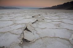 """The above photo depicts the Salt Pan of Death Valley, California at sunrise, with a view to the northward. The valley floor of Death Valley floods periodically with salt-laden water; when the water evaporates, it precipitates the salt. The polygons form by cracking of the playa surface as it dries, and stand out in relief because new salt precipitates in the cracks. """"Tepee Structure"""" forms where slabs of salt rest against each other. Photo taken January 1, 2008."""
