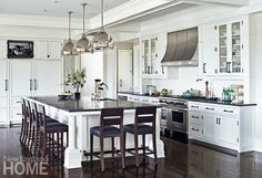 Large pendant lights loom over the vast kitchen island. The floors throughout the house are white oak with an ebony stain.
