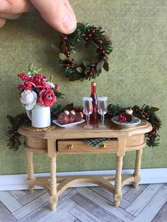 This gorgeous display of Christmas pastries, drinks and decorations is Very Merry! This piece will add some Christmas charm to your 1:12 scale dollhouse or display. Included in this listing is: 1- finely made wooden sideboard with one opening drawer 1- floral arrangement with,
