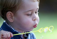 George blows bubbles at a children's party held in the grounds of Government House in Victoria, British Columbia