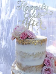 Naked wedding cake with gold leaf and fresh flowers CLOSE UP