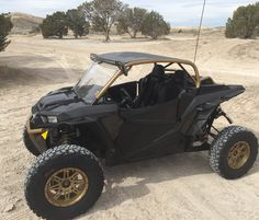"2016 Polaris RZR 1000 Turbo built by Vent Racing. It has a custom height Vent Racing Trucker cage, custom roof with 126 3"" louvers, single row LED light bar, full windshield, low-pro front bumper, Aero slip-on exhaust, Zbroz Racing ARSFX 2""+ front A-arms and high clearance rear radius rods, Pro Armor lower doors, custom black and gold Venom bucket seats by Triple X, 15x7 Sedona Badland wheels, 31x10.5x15 Dick Cepek Extreme Country tires, with custom gold powder coat."