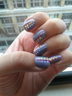 Multicolored, multi sized dot columns of varying lengths placed in alternating sequences around the nail