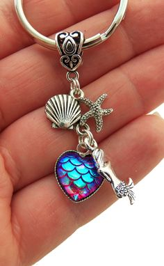 Iridescent heart shaped mermaid scale keychain with dangling seashell and starfish
