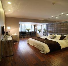 Master bedroom with wood floor and tufted headboard.
