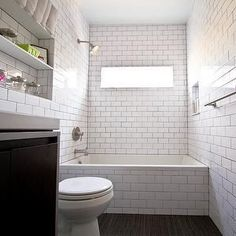 Contemporary bathroom with subway tiled drop-in tub with subway tile shower surround with black grout and shower niche filled with bath accessories. Subway Tile Showers, Bathroom Colors, Bathroom Tile Designs, White Subway Tile, Tiled Bath Panel, White Subway Tile Bathroom, Tile Bathroom, Tub Tile, White Subway Tiles