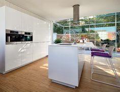 Cuines SANTOS | Minos. L'encimera Ferrostone blanca i estesa, proporciona un espai que es pot utilitzar com a taula auxiliar i, a més a més, afavoreix la uniformitat del color de l'illa.
