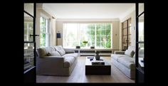 Living room with beautiful thin, classical steel doors by Costermans Projecten.
