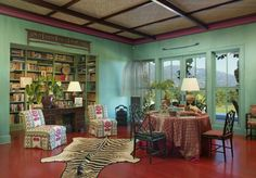 living room with safari decor tiger rug, plants, wooden chair, couchm green wall of Bring Wildness in Your Safari Rooms