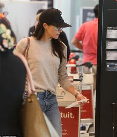 Opting for comfort over style the actress paired a pair of distressed jeans with a oatmeal-coloured cashmere jumper from Everlane as she prepared to board