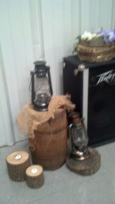 Old wooden barrel with wooden candle holders, lantern, burlap, and slices of wood.