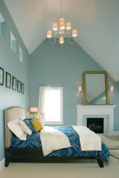Maison Luxe; love the severe slant of vaulted ceiling and mirror on fireplace. Also, robin egg  blue paint, is vey peaceful.