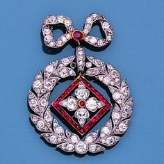 A belle epoqué diamond and ruby brooch/pendant, circa 1905 Designed as a garland tied with a ribbon bow, millegrain-set throughout with old brilliant and single-cut diamonds, the flowerhead swing centre within a lozenge-shaped border of calibré-cut rubies, detachable brooch fitting, one diamond deficient, length 4.0cm.