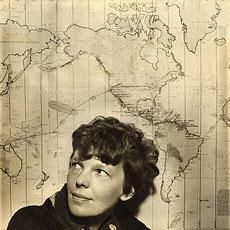 Amelia Earhart in front of a map of her proposed trip around he world