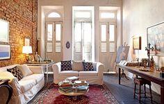 A casa tem história: construída no século 18, pertenceu à nobreza do Rio de Janeiro e nos anos 1980 virou bordel. Restaurada pelo morador Luciano Cavalcanti de Albuquerque, a sala tem parede de tijolos aparentes que lembram o passado da construção