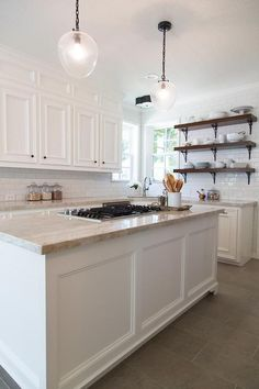 Amazing kitchen features white cabinets paired with Taj Mahal Quartzite countertops and a white subway tiled backsplash.