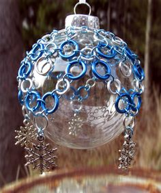 These hand-crafted chainmail ornament covers will bring a medieval elegance to your home!  Each chainmail ornament cover comes with a clear shatterproof bulb that's equipped with a silver cap and a ready-to-hang white ribbon.  Product Features    Material: Our Chainmail Ornament Covers are made from the finest bright aluminum and anodized aluminum rings. Size: The ornament cover will fit any standard size Christmas bulb. Accessories: Five snowflake charms.  Price: $25.00