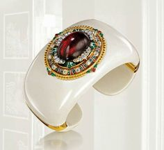 Verdura 18k yellow gold hinged mammoth ivory cuff set with antique Holbeinesque brooch. 18k yellow gold mounting, circa 1870, centering oval cabochon garnet set with 36 old-mine and rose cut diamonds and multi-colored enamel.