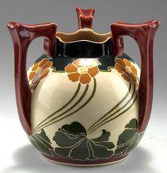 Johann von Schwarz, Nuremberg. Vase with three handles, pansies, c1900. H. 16.4 cm; D. 17 cm. Earthenware, polychromatic glaze. Marked: 2565, XXVII, B 1002.