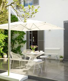 Give your outdoor space a fresh face by sticking to a monochromatic palette. You can pull off a polished look without overdoing it. Choose the essential pieces (wirework round table, umbrella, stools) in a contemporary gray and white color scheme.