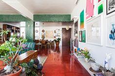 A sala de estar desse apê tem piso de cimento queimado vermelho e  pastilhas verdes na vigas e colunas.