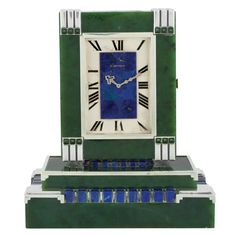Art Deco Nephrite Jade, Lapis and Sterling Silver Partners Clock, Cartier, France.   Stem wind and set, the nephrite jade clock centering on both sides in rectangular silver-tone dial with black Roman numerals, a rectangular plate. Top composed of lapis mosaic, framed by sterling silver, & edged bands tipped by Sugarloaf nephrite jade cabochon. Dial  signed Cartier, Made in France ,  with French hallmarks . 8 1/4 x 4 1/2 to 7 1/8 x 5 inches.