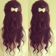 Messy dark brown curls, half up and a little bow clip.