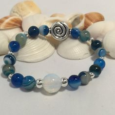 Erin Blue Striped Agate Beaded Stack Bracelet with Sterling Silver and Opaline Focals $50 This beautiful bracelet is great all by itself or stacked with some of the Chrysocolla bracelets. So buy a bunch, and mix them up! Made from all natural blue striped agate (8mm) with sterling silver beads, Sterling silver swirl and Opaline Focals. All of my stretch bracelets are made with 14 pound test weight 1mm elastic cord, that I pre-stretch to make sure they will last and never stretch o...