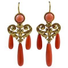"""Antique Coral Gold Girandole Earrings. Graceful coral and 15K gold girandole earrings with an elegantly decorated heart shaped central piece. """"Girandole"""" is defined as a brooch or earring consisting of a central ornament with usually three smaller ornaments hanging from it. The earrings measure 1 7/8"""" long and 3/4"""" at their widest point. England, circa 1860"""