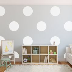 Big white polka dot wall decals placed in a pattern on a grey wall in a children's room with a bed, cabinet, and art board.