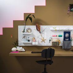 Hjemmekontor med flere hvide hulplader, vist sammen med tilbehør i hvidlakeret stål, f.eks. en hylde, beholdere, klemmer, kroge, en rulleholder og en brevholder.