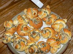 Parmesan-Garlic Knots ~ Combine 1/2 c. margarine (melted), 1/4 c. grated parmesan cheese, 1.5 tsp parsley flakes, 1.5 tsp. oregano, 1 tsp. garlic powder and dash of pepper; set aside. Cut each biscuit in half (3 cans (12 oz) refrigerated biscuits. Roll each portion into a rope; tie in a loose knot.  Place on greasd baking sheet. Bake at 450 degrees for 6-8 min or unil golden brown. Immediately brush with parmesan mixture.  Remove from cookie sheet. Brush again with cheese mixture.