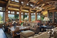 living room of rustic mountain luxury timber frame home with traditional interior design