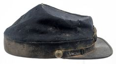 "Union Infantry Officer's Kepi  Dark blue wool blue body with black velvet band. Finish very worn. Black enameled bound leather on pasteboard visor lined in green grained leather; black enameled leather chin strap with brass wire buckle and eagle side buttons.  Obverse has applied gold bullion embroidered infantry bugle insignia on wool with false bullion metal regimental numbers ""17.""  Interior has gauze lining with leather crow"