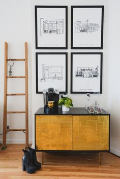 Man Repeller's beverage station does double-duty as a morning-coffee and evening-cocktail bar. A quartet of local coffee shop prints hanging above continue the java theme while personalizing the space. Beyond the drinking accoutrements, the console is bare but for a Jonathan Adler Gold Muse Candle, and a wooden ladder serves as a magazine or jewelry rack just to the side.  Photo by Claire Esparros via Style Me Pretty