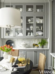 Traditional touches give a new high-rise apartment a sense of permanence. Pendant, Ralph Lauren Home for Circa Lighting; chairs, Mainly Baskets; cabinetry in Plummett, Farrow & Ball.