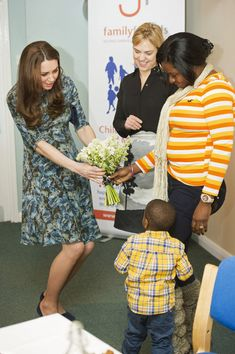 Catherine, Duchess of Cambridge meets 2-year-old Ryan and his mother Tracy Dixon who presented her with flowers as she attends a coffee morning at Family Friends in Kensington on January 19, 2015 in London, England.