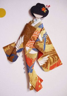 Handmade card with Japanese origami paper doll.  Materials: Card stock with Japanese print; kimono and obi (yuzen washi); viscose cord on obi; hair decor (nail sticker and bud sticks).  Card dimensions: 17.4 cm x 12.6 cm Doll height: 10.5 cm