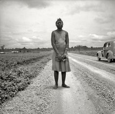 "July 1936. ""Mississippi Delta. Negro woman carrying her shoes home from church."""