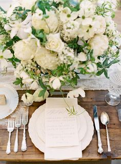 Very classical looking. Antique silver cuttlery, white china, cream flowers with delicate greenery. Wooden table with vintage white runner