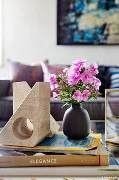 Coffee table styled with books, clock, and flowers