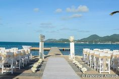 white columns with orchids arrangments , white carpet , white flowers, folding chairs decorated with gold sashes made by www.fee-des-caraibes.com Face book: Mariages À Saint Martin
