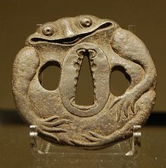 Tsuba -- handguard (between the handle and blade  of a sword), Japanese. A whimsical frog who seems to be quite happy.