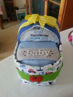 <3 Small Bassinet Nappy Cake <3  Contains – 25 Infant Nappies  1 x Baby Singlet 0000  1 x Winter Jumpsuit 0000  1 x Flannelette Baby Wrap  1 x Over-the-shoulder Burp Cloth  1 x Baby Wash Cloth  Decorated/Embellished  Finished with Cellophane & Ribbon    https://www.facebook.com/shaleagiftboxes?ref=hl
