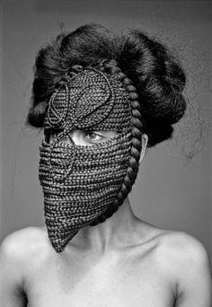 photo africaine noir et blanc : Delphine Diallo, femme artiste sénégalaise, masque, tresses, coiffure